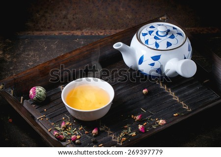 Traditional japanese teapot and cup of green tea, served on bamboo tray with dry tea variations over dark background - stock photo