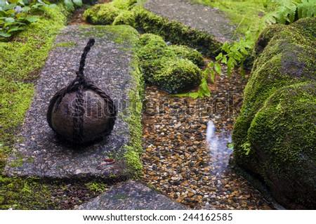 Traditional japanese weight in zen garden - stock photo