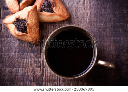 Traditional jewish Hamantaschen cookies for Purim  and coffee in ancient cup on a wooden table - stock photo