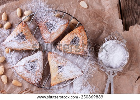 Traditional jewish Hamantaschen cookies for Purim with sugar powder on brown paper - stock photo