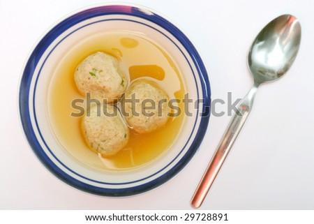 Traditional Jewish matzah ball soup, dumplings made from matzah meal - ground matzo. - stock photo