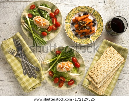 Traditional Jewish Passover dishes of Gefilte Fish and Tsimmes with red wine and matzah on white wood - stock photo