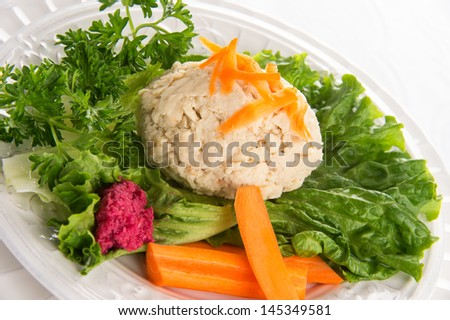 Traditional Jewish passover food gefilte fish with carrots, parsley, horseradish, and lettuce on white linen table cloth