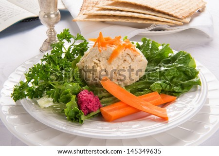 Traditional Jewish passover food gefilte fish with carrots, parsley, horseradish, and lettuce on white linen table cloth with matzah, Kiddush cup and haggadah in background - stock photo