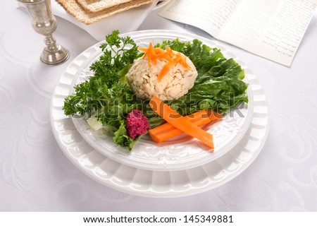 Traditional Jewish passover food gefilte fish with carrots, parsley, horseradish, and lettuce on white linen table cloth with matzah, Kiddush  in background - stock photo