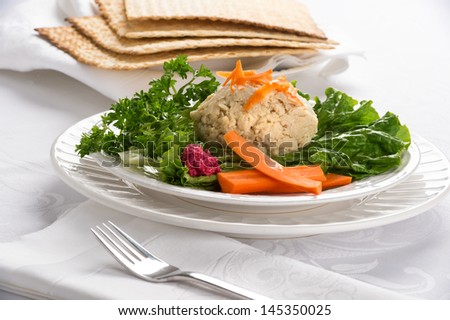 Traditional Jewish passover food gefilte fish with carrots, parsley, horseradish, and lettuce on white linen table cloth with matzah in background - stock photo