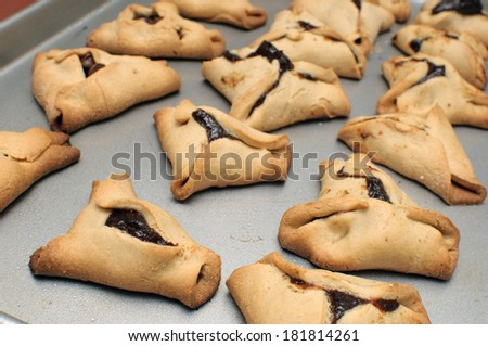 traditional Jewish pastry for purim, handmade with prune filling. Selective focus on closest row. - stock photo
