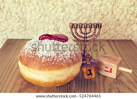 Traditional Jewish sweet donuts and other symbols for Hanukkah holiday. Selective focus. Image toned for inspiration of retro style