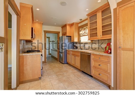 Traditional kitchen with stainless steel fridge and tile floor.