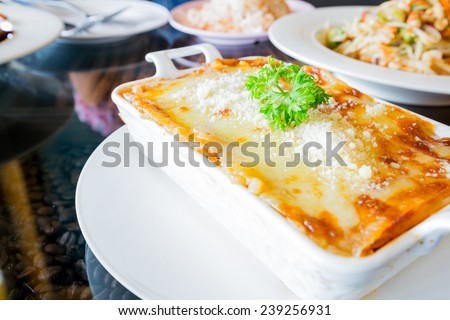 traditional lasagna made with minced beef bolognese sauce topped with basil leafs - stock photo