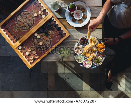Traditional Lebanese cafe in Beirut: table with backgammon and meze plate and falafel , female hand with pita, view from above