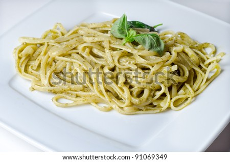 Traditional linguini with basil pesto on a white plate - stock photo
