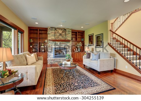 Traditional living room with decorative rug and hardwood floor. - stock photo