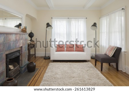 Traditional living room with white leather couch, pillows, rug, fire place and wood beams. - stock photo
