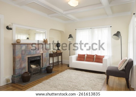 Traditional living room with white leather couch, pillows, rug, fire place, mirror and wood beams. - stock photo