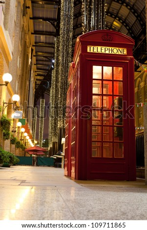 Traditional London symbol red public phone box in illuminated and festively decorated empty trade passage in evening. Great Britain - stock photo