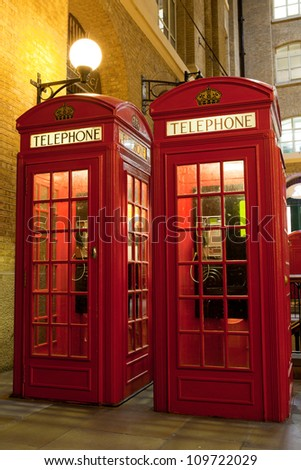 Traditional London symbol red public phone boxes at illuminated evening street. Great Britain - stock photo