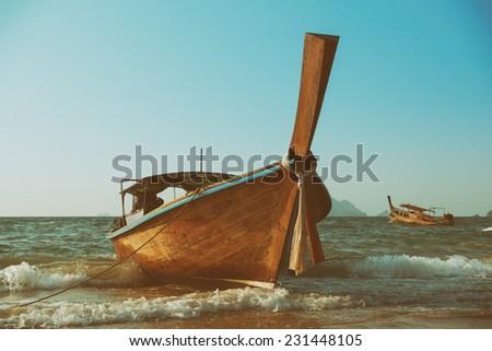 Traditional longtail wooden boat at Andaman sea, retro toned - stock photo