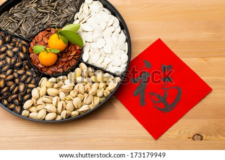 Traditional Lunar new year snack tray and chinese calligraphy, meaning for blessing good luck  - stock photo