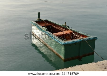 Traditional maltese boat with nice reflection on a water. Old boat with light reflections - stock photo