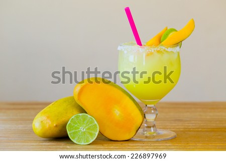Traditional mango margarita with lime at a Mexican restaurant bar. - stock photo