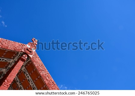 Traditional Maori house roof in red color under blue sky - stock photo