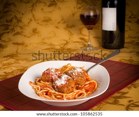 Traditional meal of Italian spaghetti and meatballs with red wine - stock photo