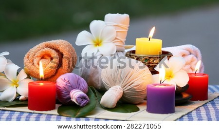 Traditional Medicine of Thailand, Herbal Ball for massage and spa decorated with frangipani and candles.