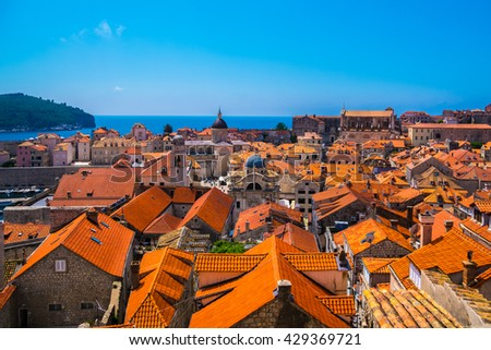Traditional Mediterranean houses with red tiled roofs and rocky green idyllic island in background,Dubrovnik,Dalmatia,Croatia,Europe - stock photo
