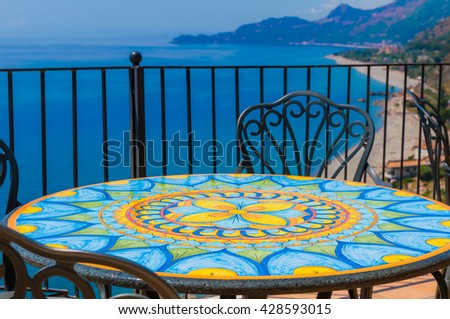 Traditional mediterranean seaside restaurant on the hillside with mosaic deacorated wrought iron tables and chairs and amazing blue sea panorama with clear blue sky, Sicily - stock photo