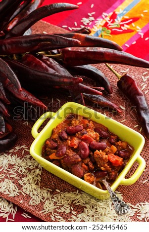 Traditional mexical chili con carne: chili with mixed meat, beans and tomatoes with dry hot papers on the background and rice. - stock photo