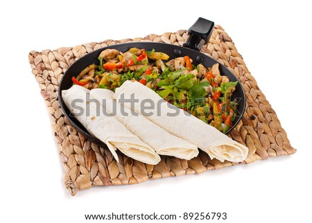 traditional mexican beef fajitas with tortillas on white background