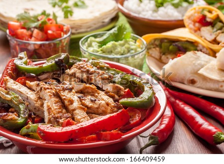 traditional mexican food: cilantro and lime rice, chicken fajitas, fajita peppers, burritos, tortillas, guacamole and salsa - stock photo