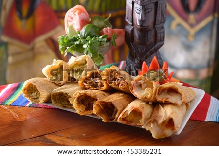 Traditional Mexican food tamales platter with garnishes with copy space - stock photo