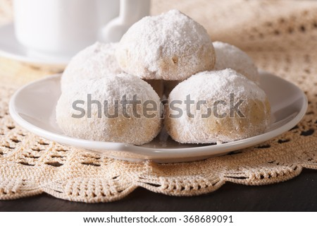 Traditional Mexican polvoron cookies with pecans and powdered sugar macro on the table. horizontal
