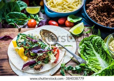 Traditional mexican tortillas or fajita recipe with ingredients on wooden table from overhead. - stock photo
