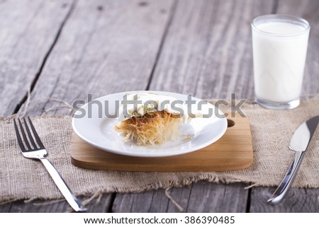 Traditional Middle Eastern dessert baklava serving with pistachio nuts , ice cream and milk for drink - stock photo