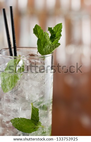 traditional mojito cocktail with fresh mint  served on a busy bar top - stock photo