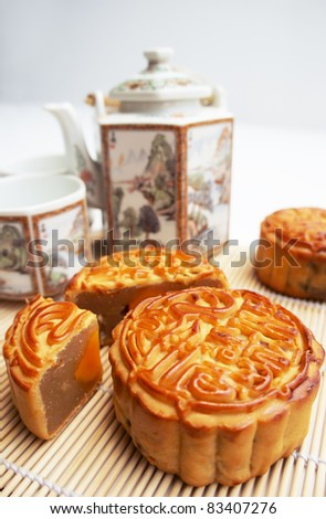 Traditional Mooncake on a mat with tea pot as background