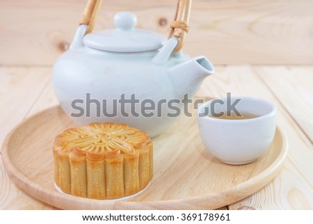 Traditional mooncake on table with teacup and teapot. Chinese mid autumn festival foods. Chinese new year. - stock photo