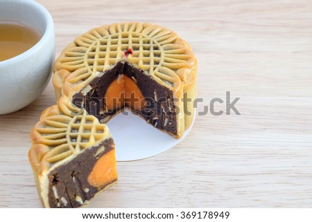 Traditional mooncakes on table with teacup. Chinese mid autumn festival foods. Chinese new year. - stock photo