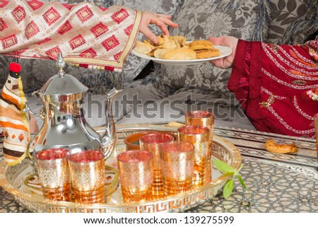 Traditional Moroccan immigrant women presenting typical Ramadan cookies and tea - stock photo