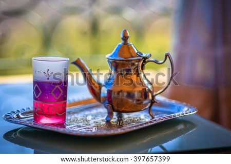 Traditional Moroccan kettle full with tea with a colorful glass cup on the metal tray
