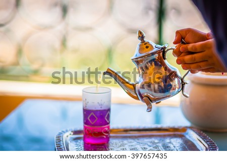 Traditional Moroccan kettle full with tea with a colorful glass cup on the metal tray, served by a woman hands