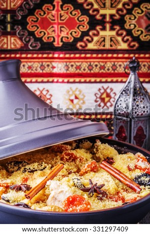 Traditional moroccan tajine of chicken with dried fruits and spices, selective focus. - stock photo