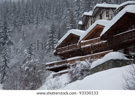 Traditional mountain chalet in snowy weather - stock photo