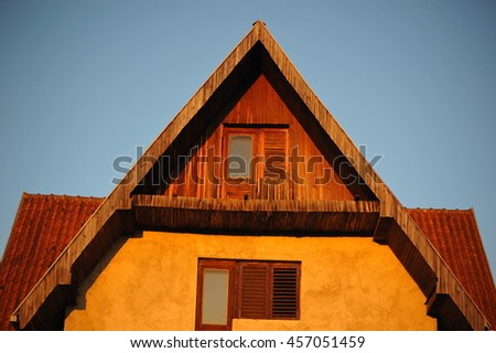 Traditional mountain house with steep tiled roof. Attic floor exterior. - stock photo