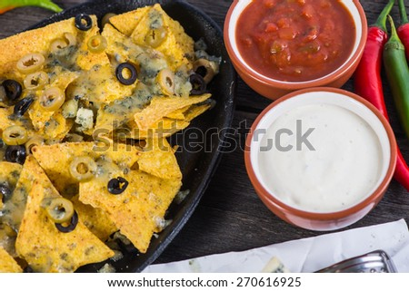 traditional nachos with cheese and salsa from above - stock photo