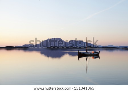 Traditional Nordland boat after sunset, with a tern sitting on top of the mast and Donna mountain on background. Photographed at Helgeland coast in Nordland county, Norway.  - stock photo