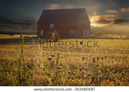 Traditional north american red barn and hay bales at sunset. - stock photo